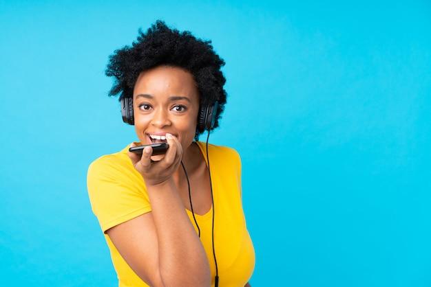 Młoda amerykanin afrykańskiego pochodzenia kobiety słuchająca muzyka z wiszącą ozdobą nad odosobnioną błękit ścianą