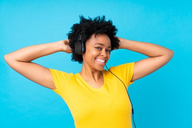 Młoda amerykanin afrykańskiego pochodzenia kobiety słuchająca muzyka z wiszącą ozdobą