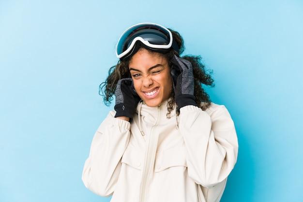 Młoda amerykanin afrykańskiego pochodzenia narciarki kobieta odizolowywał nakrywkowych ucho z rękami.
