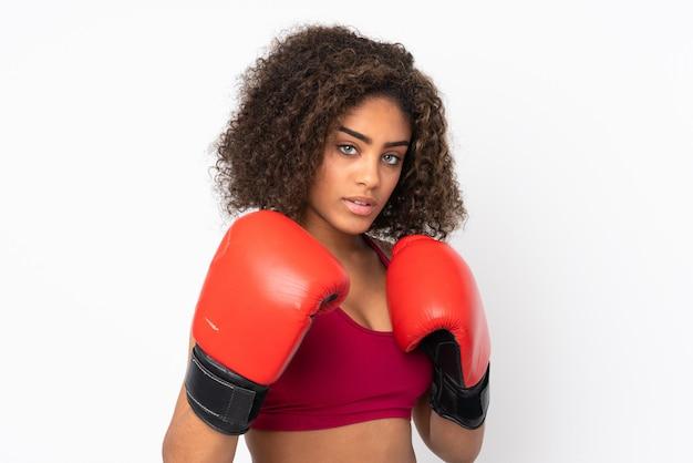 Młoda amerykanin afrykańskiego pochodzenia sporta kobieta odizolowywająca na biel przestrzeni z bokserskimi rękawiczkami