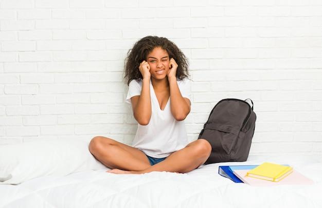 Młoda amerykanin afrykańskiego pochodzenia studencka kobieta na łóżkowym nakrywkowym ucho z rękami.