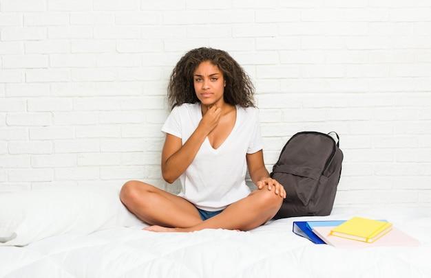 Młoda amerykanin afrykańskiego pochodzenia studencka kobieta na łóżku cierpi ból w gardle z powodu wirusa lub infekcji.