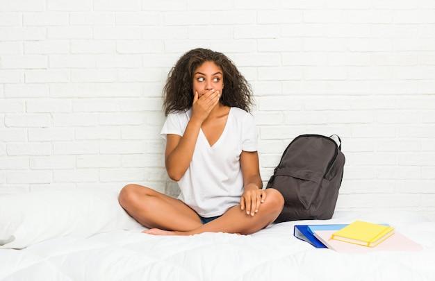 Młoda amerykanin afrykańskiego pochodzenia studencka kobieta na łóżku rozważny patrzeć odbitkowy astronautyczny nakrywkowy usta z ręką.