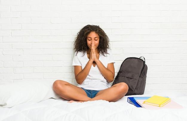 Młoda amerykanin afrykańskiego pochodzenia studencka kobieta na łóżku trzyma ręki w modli się blisko usta, czuje się pewny.