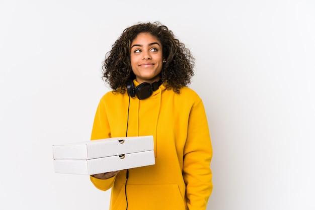 Młoda amerykanin afrykańskiego pochodzenia studencka kobieta trzyma pizze marzy osiągać cele i zamierzenia