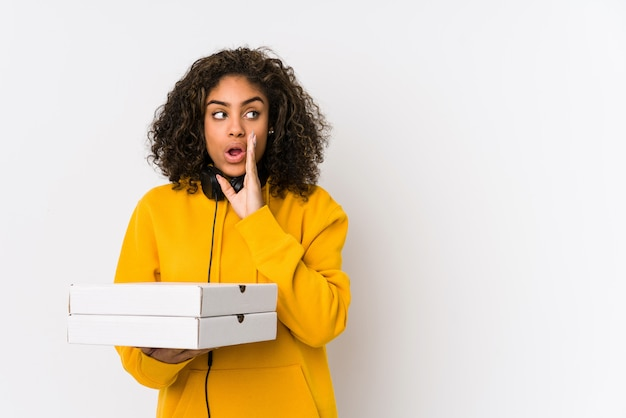 Młoda amerykanin afrykańskiego pochodzenia studencka kobieta trzyma pizze mówi tajną gorącą hamującą wiadomość i patrzeje na boku