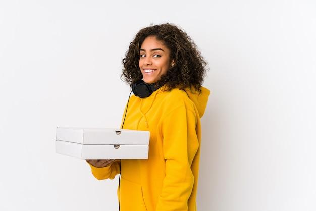 Młoda amerykanin afrykańskiego pochodzenia studencka kobieta trzyma pizze patrzeje na boku uśmiechniętego, rozochoconego i przyjemnego.