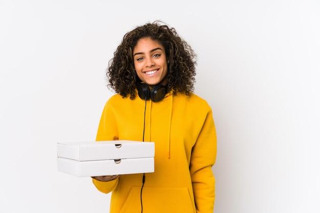 Młoda amerykanin afrykańskiego pochodzenia studencka kobieta trzyma pizze szczęśliwe, uśmiechnięte i wesołe.