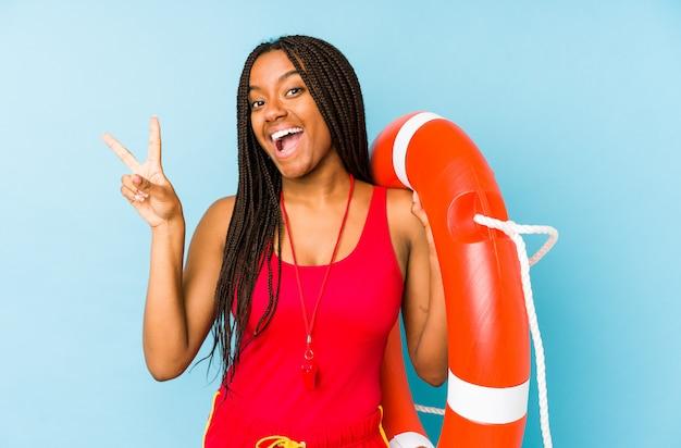 Młoda amerykanin afrykańskiego pochodzenia życia ratownika kobieta odizolowywał radosnego i beztroskiego pokazywać pokoju symbol z palcami.