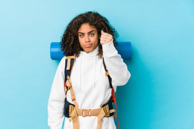 Młoda amerykanina afrykańskiego pochodzenia backpacker kobieta pokazuje pięść kamera, agresywny wyraz twarzy.