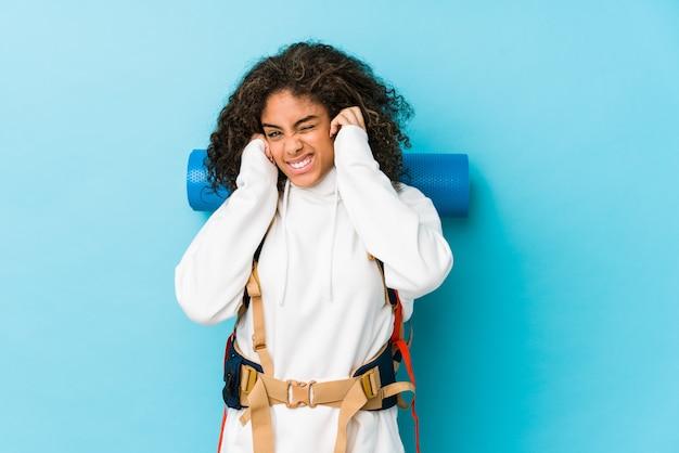 Młoda amerykanina afrykańskiego pochodzenia backpacker kobieta zakrywa ucho z rękami.