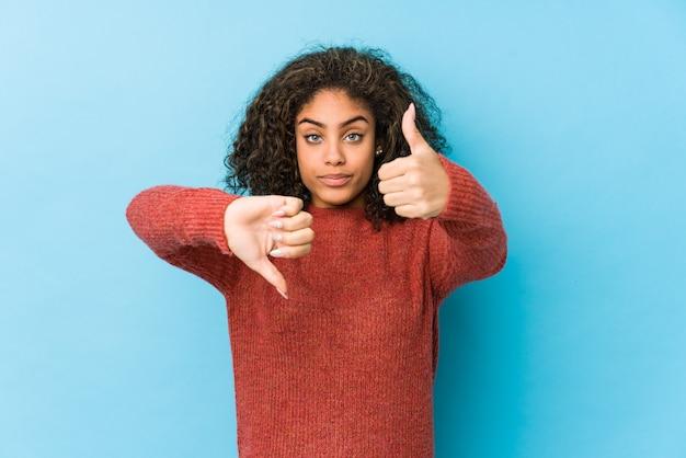 Młoda amerykanina afrykańskiego pochodzenia kędzierzawego włosy kobieta pokazuje aprobaty i kciuki zestrzela, trudny wybiera pojęcie