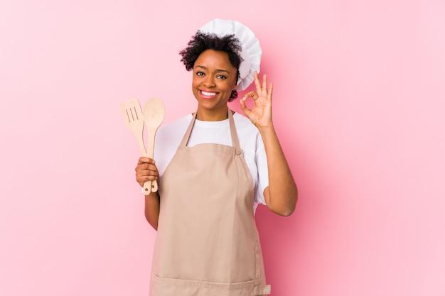 Młoda amerykanina afrykańskiego pochodzenia kucharza kobieta rozochocona i ufna pokazuje ok gest.