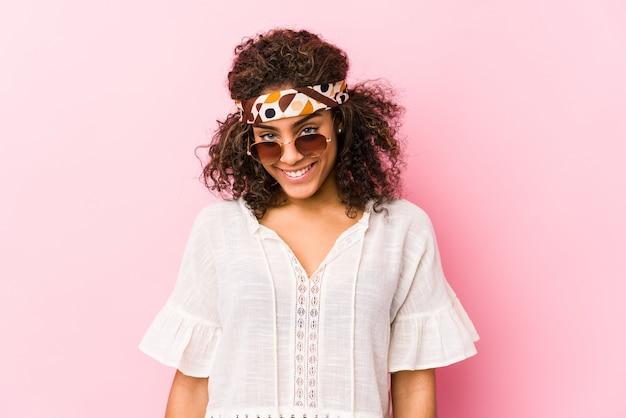 Młoda amerykanina afrykańskiego pochodzenia modnisia kobieta d na menchii ścianie szczęśliwej, uśmiechniętej i rozochoconej.