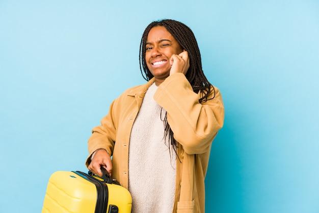 Młoda amerykanina afrykańskiego pochodzenia podróżnika kobieta trzyma walizkę odizolowywał nakrywkowych ucho z rękami.
