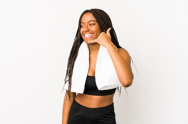 Młoda amerykanina afrykańskiego pochodzenia sporta kobieta odizolowywająca pokazywać telefonu komórkowego wezwania gest z palcami.