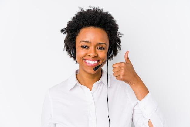 Młoda amerykanina afrykańskiego pochodzenia telemarketer kobieta odizolowywał uśmiecha się kciuk up i podnosi