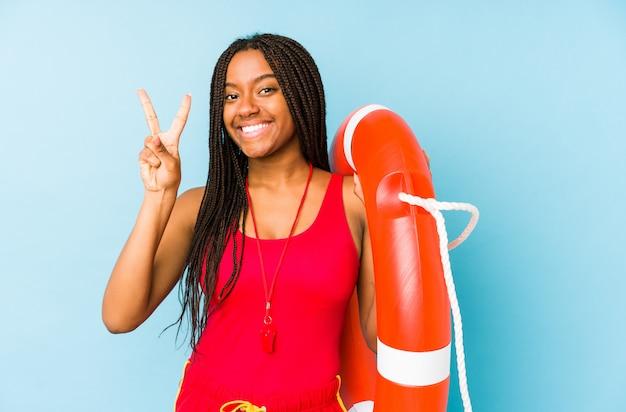 Młoda amerykanina afrykańskiego pochodzenia życia strażnika kobieta odizolowywał pokazywać numer dwa z palcami.