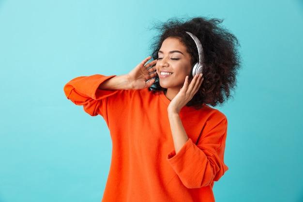 Młoda amerykanka w wieku 20 lat z kudłatą fryzurą słuchająca muzyki przez bezprzewodowe słuchawki podczas słuchania ulubionej melodii, odizolowana na niebieskiej ścianie