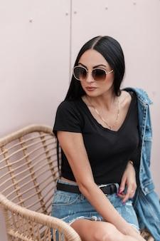 Młoda amerykanka z długimi włosami w okularach przeciwsłonecznych w stylowej dżinsowej kurtce w czarnej koszulce siedzi na krześle przy różowej ścianie na tarasie letniej kawiarni. stylowa seksowna hipster dziewczyna na zewnątrz.