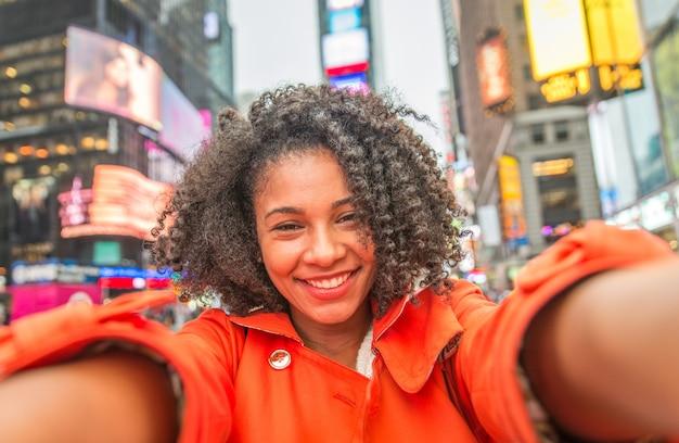 Młoda amerykańska kobieta bierze selfie w nowy jork, czasu kwadrat