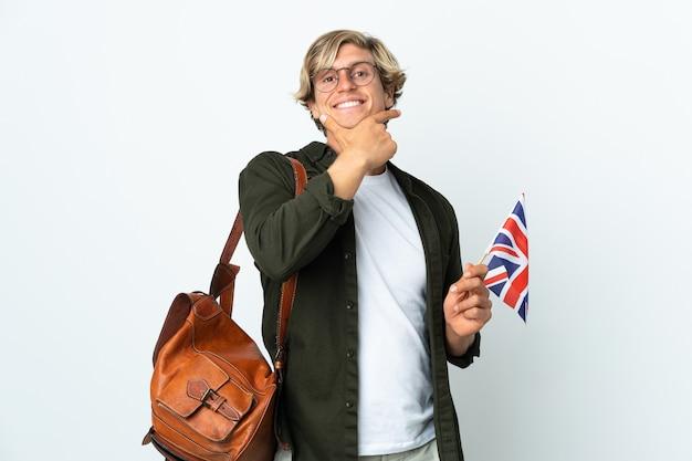 Młoda angielka kobieta trzyma flagę zjednoczonego królestwa szczęśliwa i uśmiechnięta