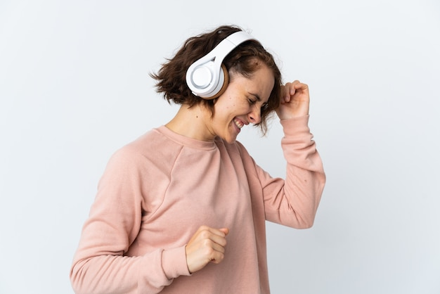 Młoda angielka na białym słuchanie muzyki i tańca