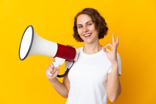 Młoda angielka na żółtej ścianie trzyma megafon i pokazuje znak ok palcami