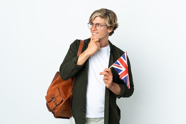 Młoda angielska kobieta trzyma flagę zjednoczonego królestwa, patrząc z boku i uśmiechnięta