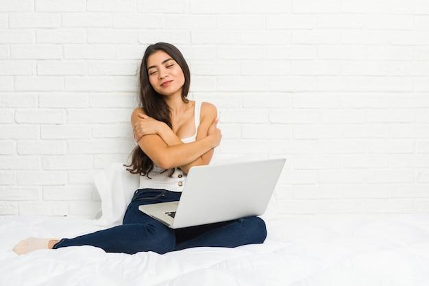 Młoda arabka pracująca z laptopem na łóżku przytula, uśmiechnięta beztrosko i szczęśliwa.