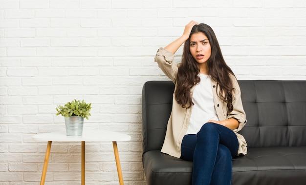 Młoda arabka siedząca na kanapie będąc w szoku, przypomniała sobie ważne spotkanie.