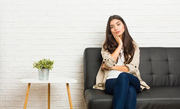 Młoda arabka siedzi na kanapie, która jest znudzona, zmęczona i potrzebuje dnia relaksu.