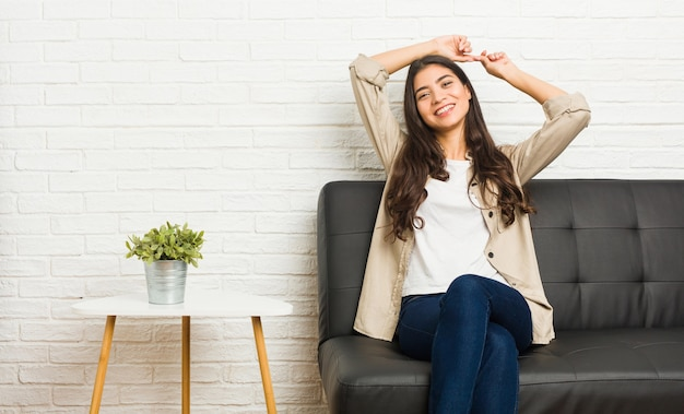 Młoda arabka siedzi na kanapie, rozciągając ramiona, zrelaksowana pozycja.