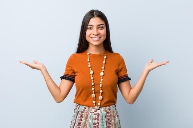 Młoda arabka sprawia, że skala z rękami, czuje się szczęśliwa i pewna siebie.