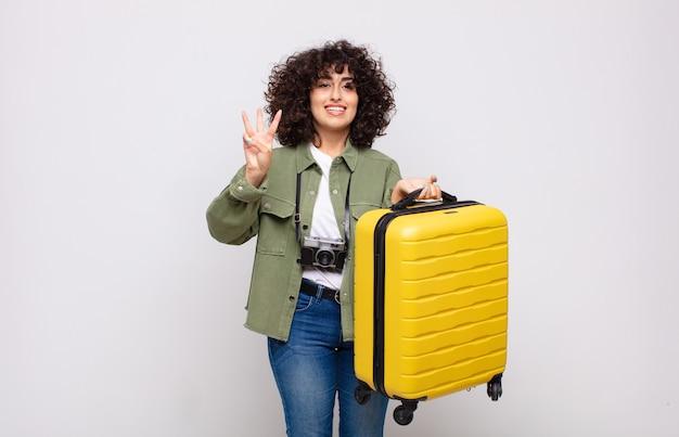 Młoda arabka uśmiechnięta i wyglądająca przyjaźnie, pokazująca numer trzy lub trzeci z ręką do przodu, odliczając koncepcję podróży