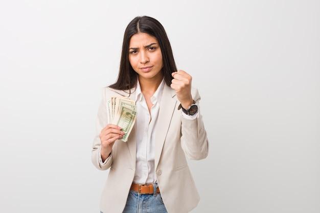 Młoda arabska biznesowa kobieta trzyma dolary pokazuje pięść z agresywnym wyrazem twarzy.