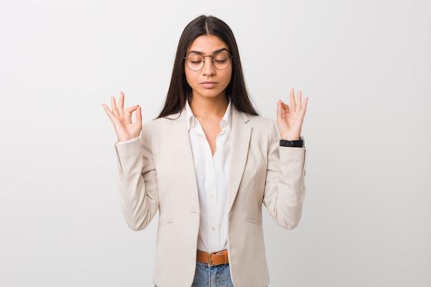 Młoda arabska kobieta biznesu na białym tle na białym tle relaksuje się po ciężkim dniu pracy, wykonuje jogę.