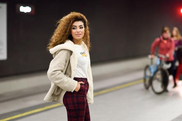 Młoda arabska kobieta czeka jej pociąg w staci metru.