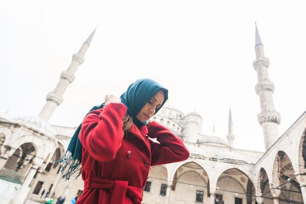 Młoda arabska kobieta jest ubranym przesłonę przed meczetem w istanbuł
