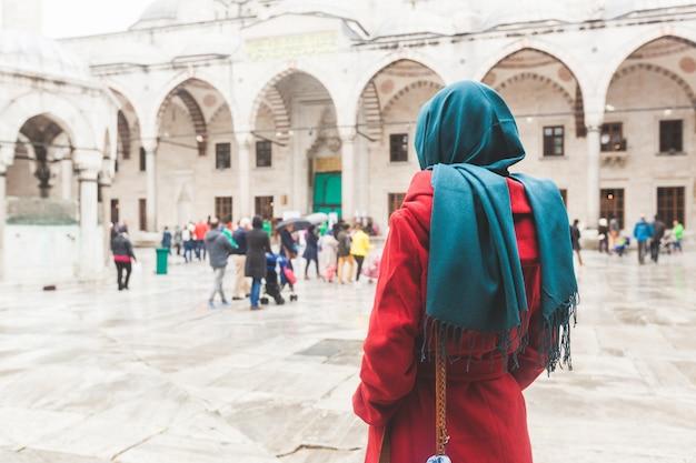 Młoda arabska kobieta jest ubranym zasłonę przed meczetem