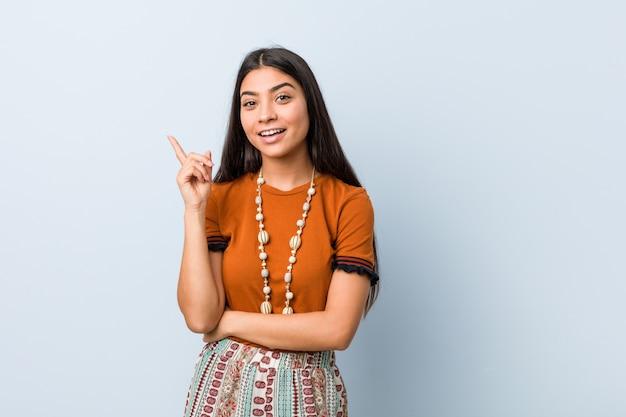Młoda arabska kobieta ono uśmiecha się radośnie wskazujący z palcem wskazującym daleko od.