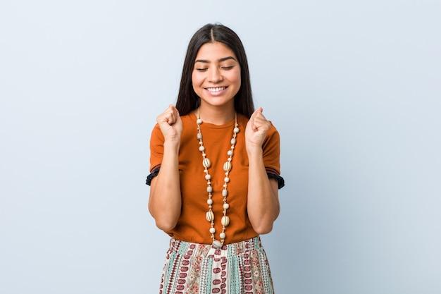 Młoda arabska kobieta podnosząc pięść, czując się szczęśliwy i udany. koncepcja zwycięstwa.