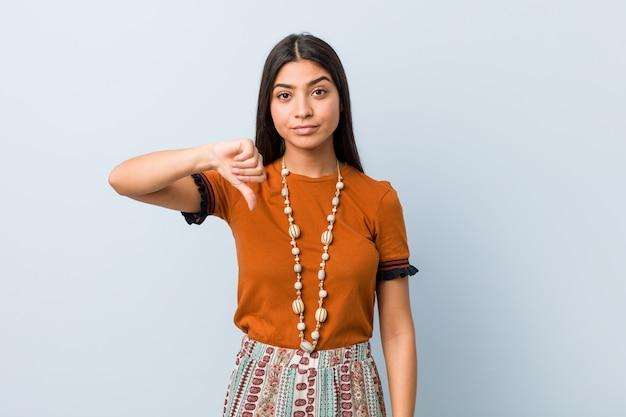 Młoda arabska kobieta pokazuje niechęć gest, kciuki w dół. pojęcie nieporozumienia.