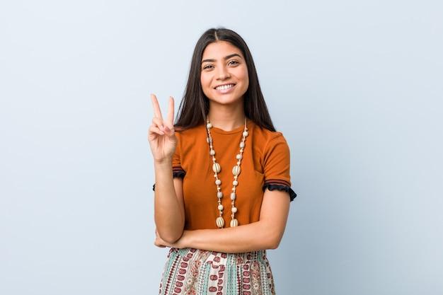 Młoda arabska kobieta pokazuje numer dwa z palcami.