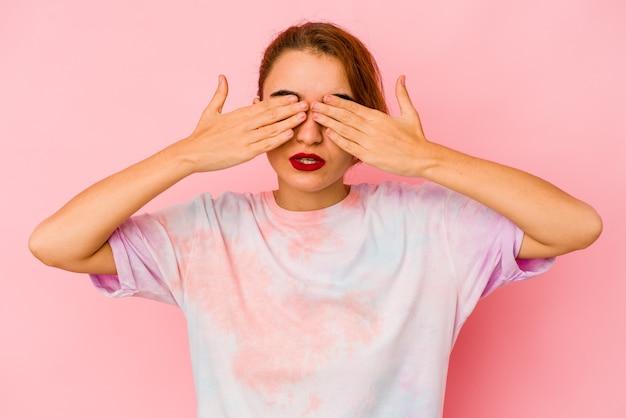 Młoda arabska kobieta rasy mieszanej boi się zakrywających oczy rękami.