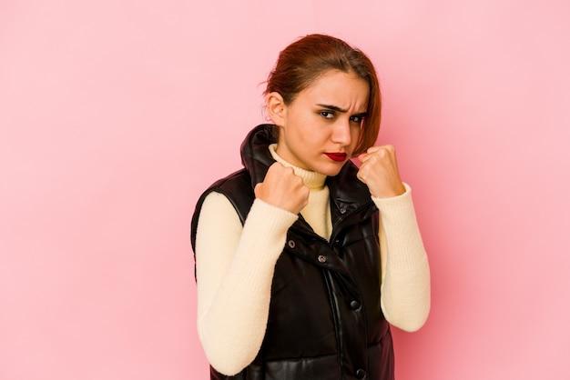 Młoda arabska kobieta rasy mieszanej pokazująca pięść do kamery, agresywny wyraz twarzy.