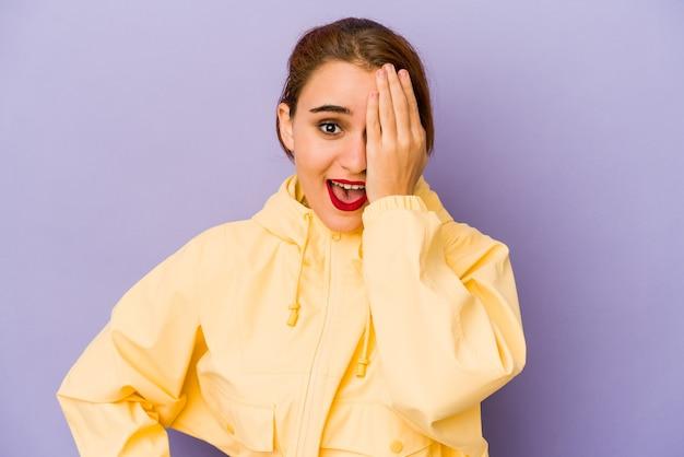 Młoda arabska kobieta rasy mieszanej zabawy obejmujące połowę twarzy dłonią.