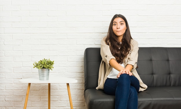 Młoda arabska kobieta siedząca na kanapie wzrusza ramionami i ma zdezorientowane oczy