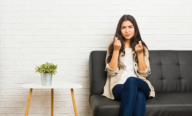 Młoda arabska kobieta siedzi na kanapie, pokazując, że nie ma pieniędzy.