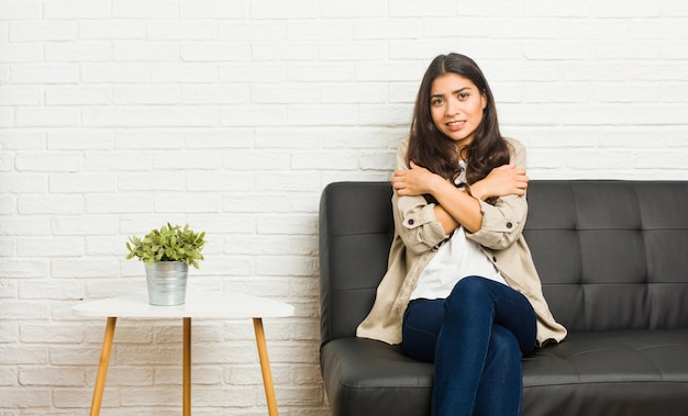 Młoda arabska kobieta siedzi na kanapie, stygnie z powodu niskiej temperatury lub choroby.